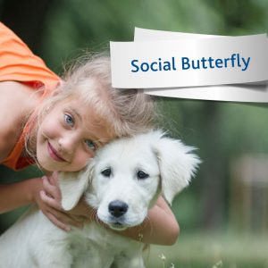 Girl hugging a puppy, label entitled Social Butterfly